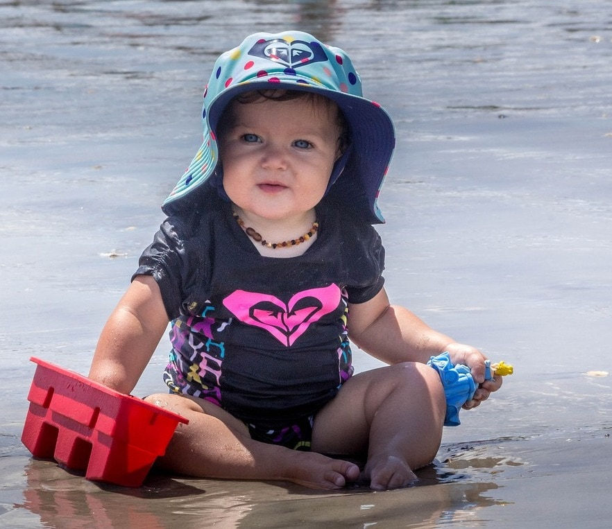 Baby wears sun-protective clothing at the beach.