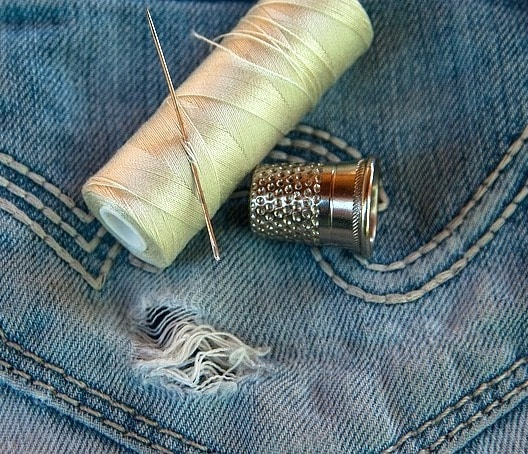 Needle and thread with jeans.