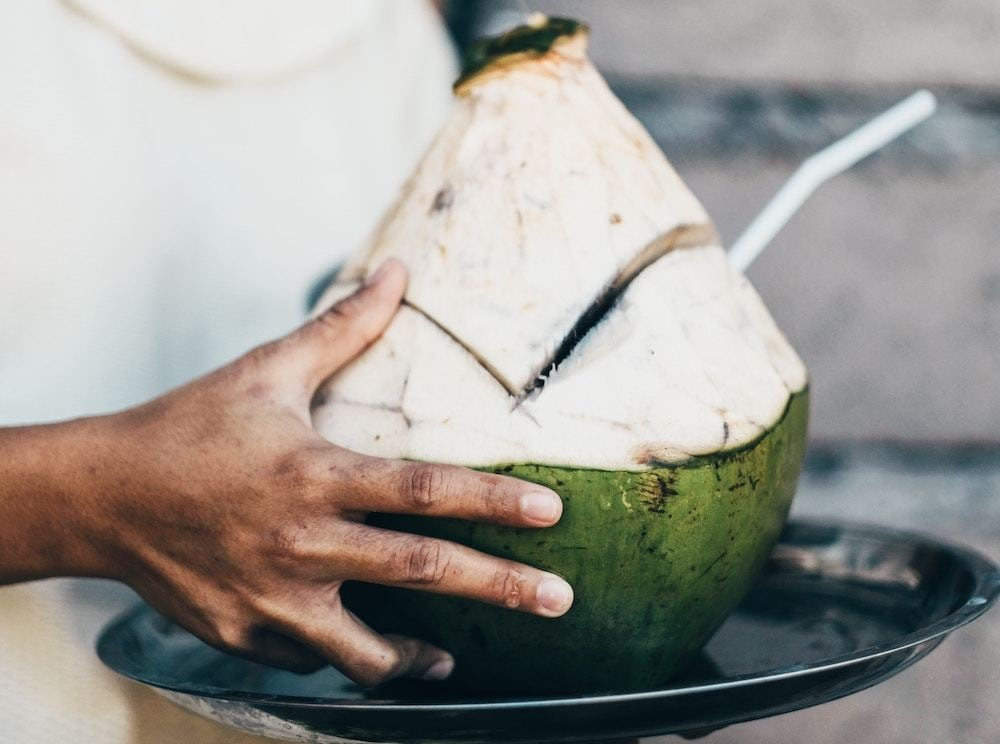 Woman holding coconut with straw