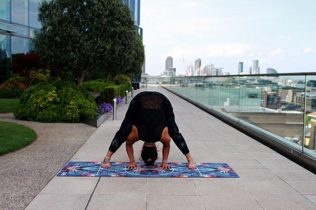 Woman practices inversion yoga pose on an outdoor terrace