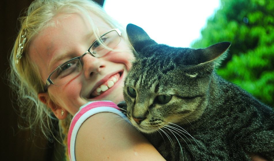 little girl with glasses hugging cat