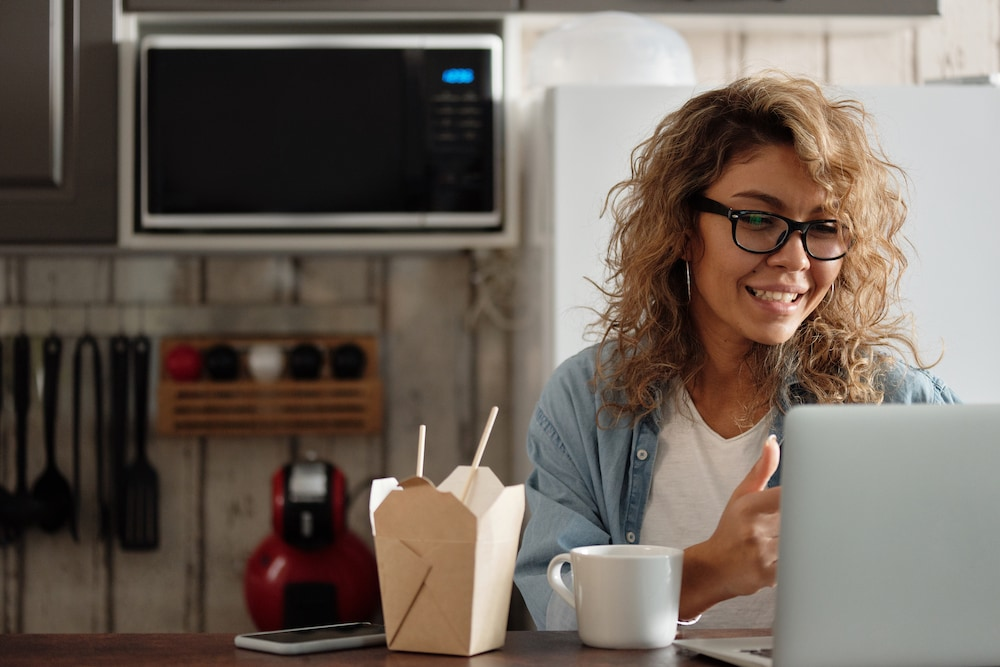 Woman in kitchen on video call with takeout