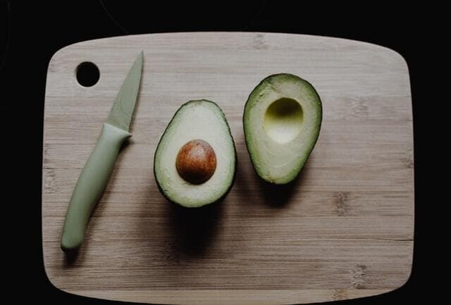 avocados on a cutting board with knife