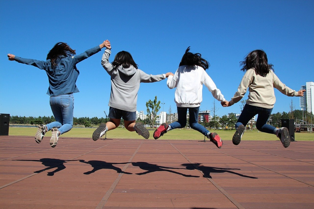 Four girls jump on school track outside