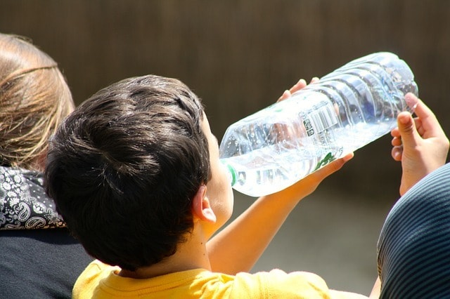 young boy drinking from disposable plastic water bottle