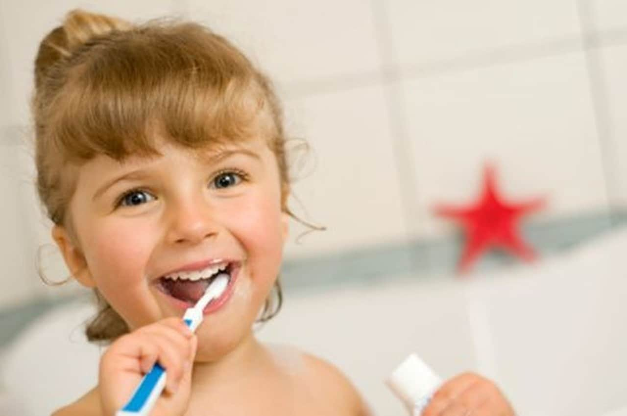 girl brushing teeth with natural toothpaste