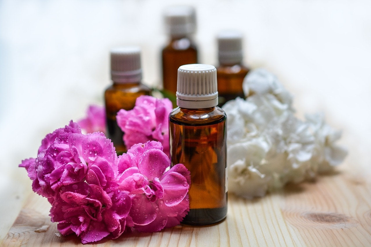 Four bottles of essential oils sitting on table with flowers