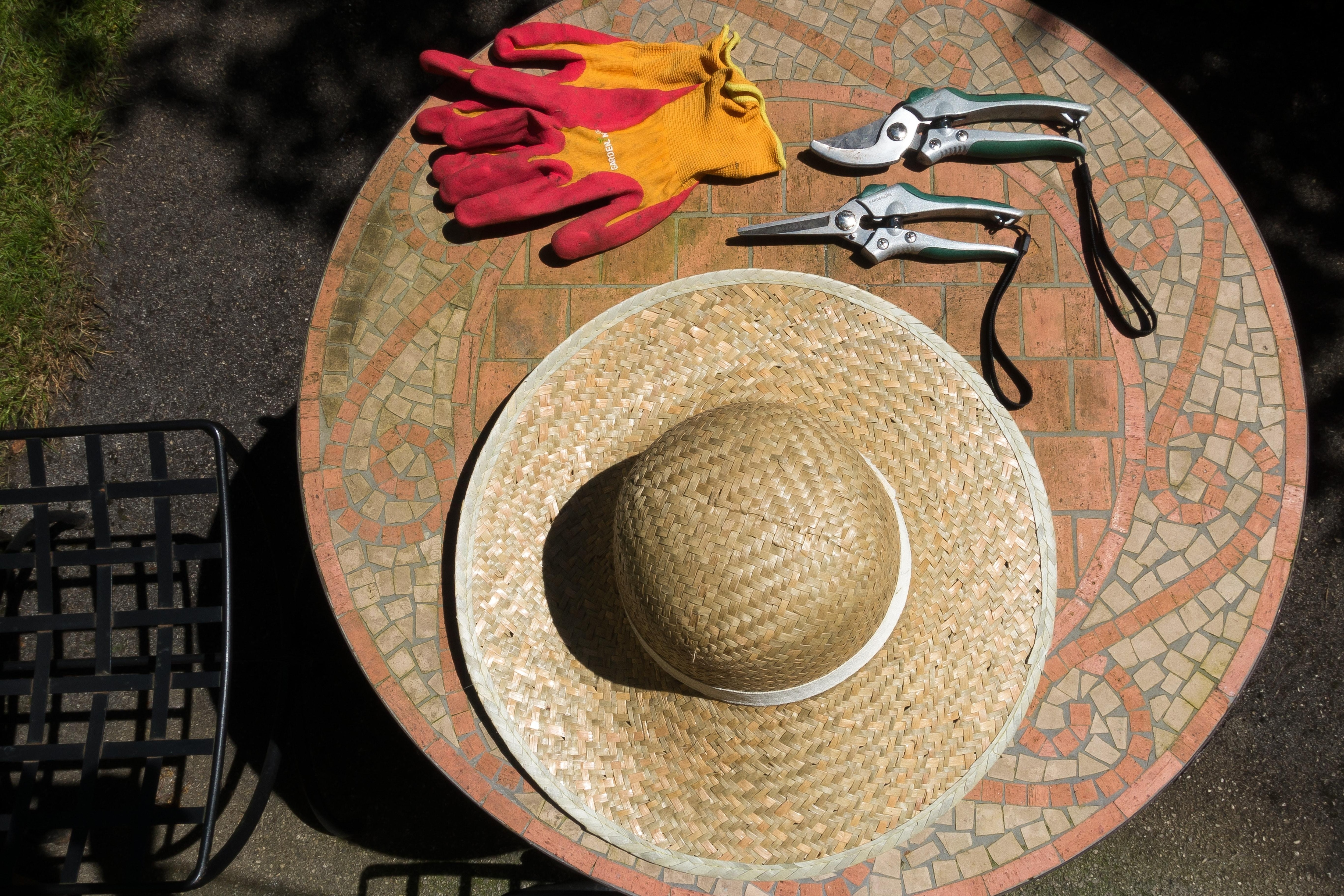 Gardening tools, including a woven hat, gloves, and pruners, sit on an outdoor table