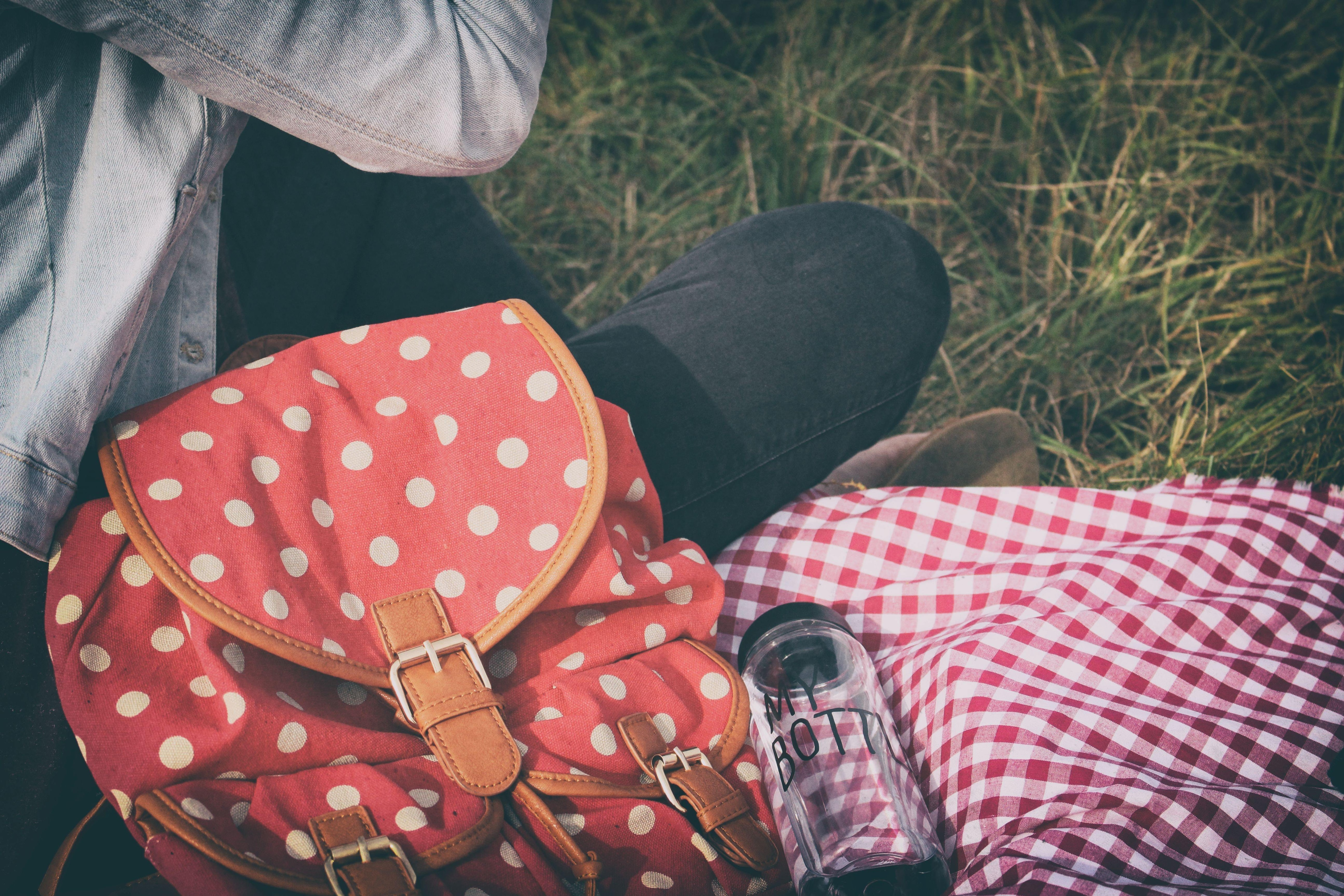 Woman sitting on a read and white checked picnic planket with a plastic water bottle and a backpack