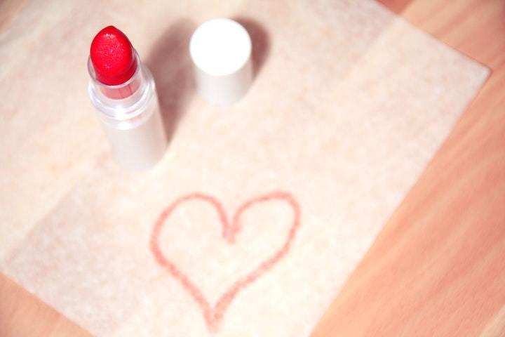 Tube of lipstick on table with heart drawn on napkin
