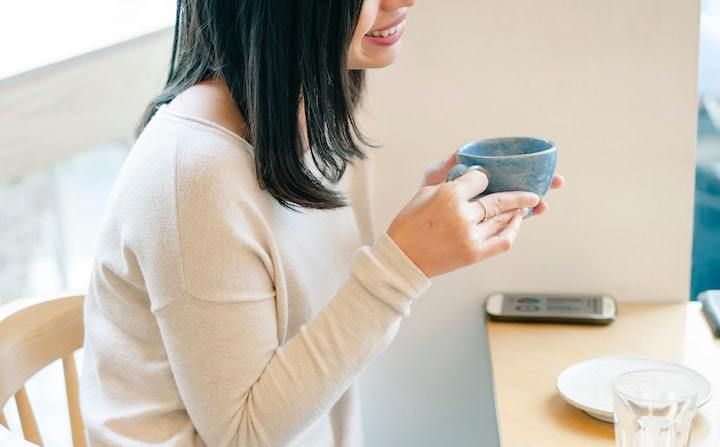 Woman smiling with mug of coffee at breakfast table