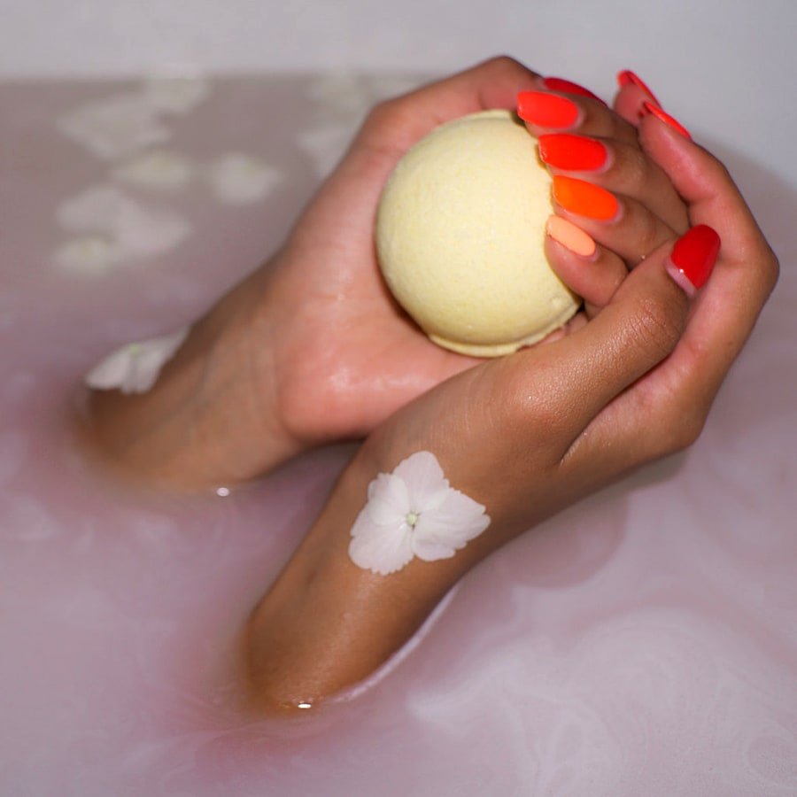 woman's hands holding a bath bomb in the the bathtub