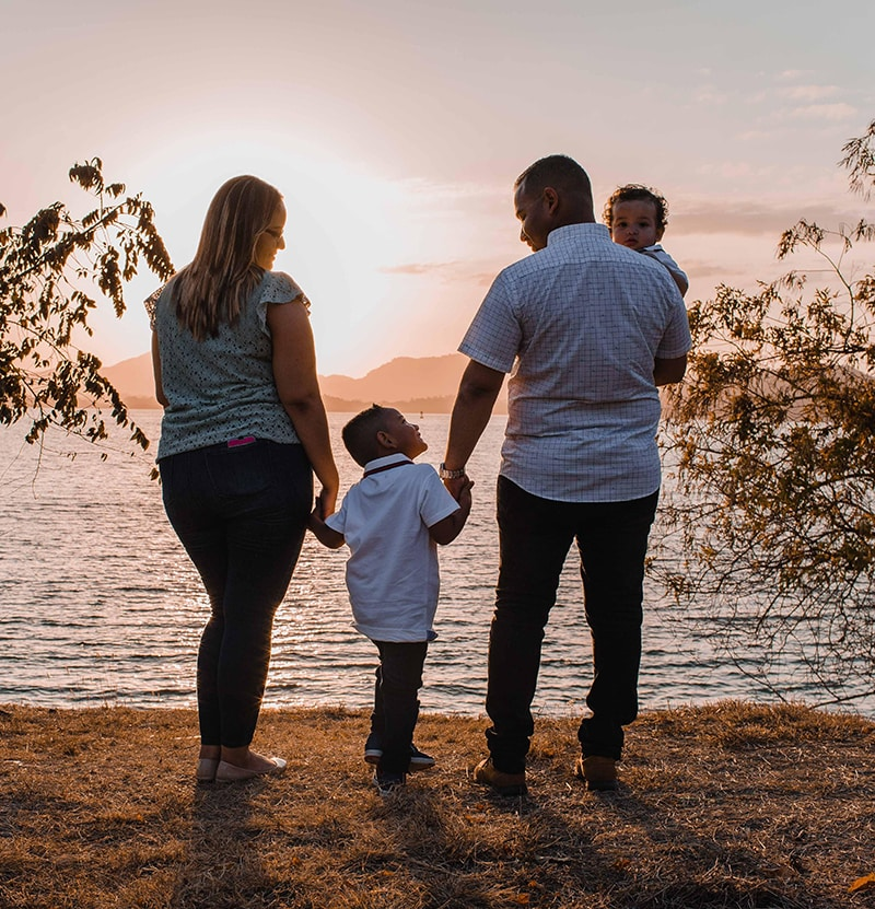 Family with children watches a sunset over a lake.
