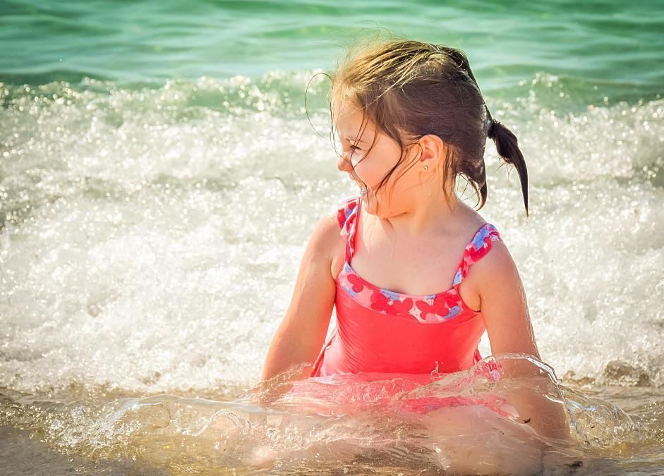 little girl giggling in an ocean wave