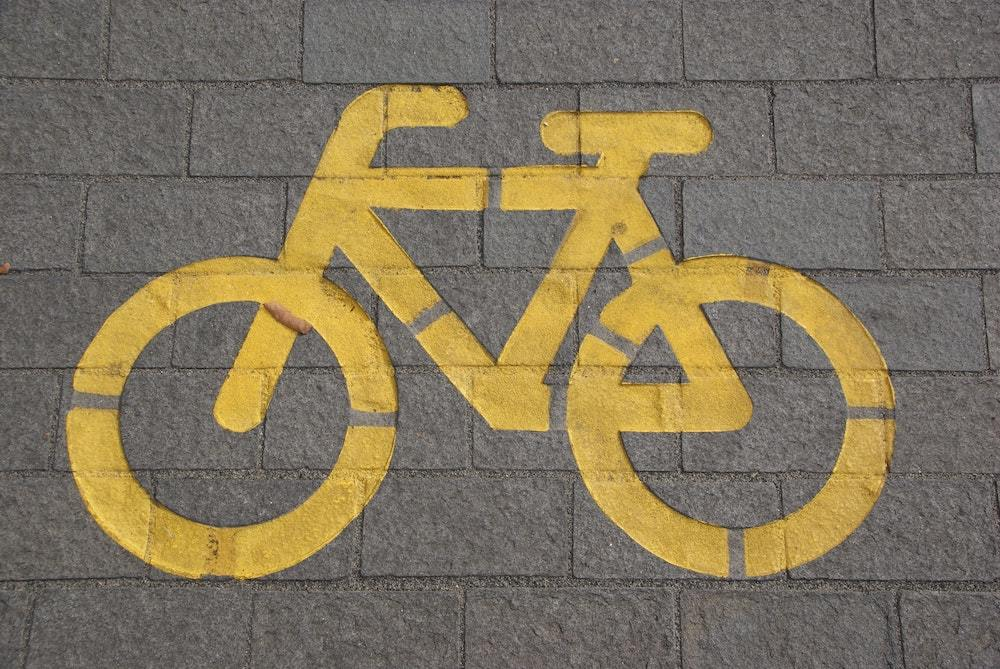 yellow bike lane symbol on brick pavers