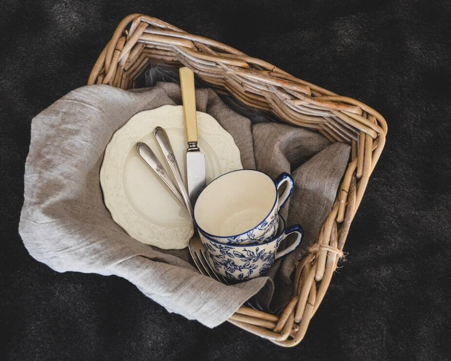 basket containing 2 mugs, silverware, plate and tea towel