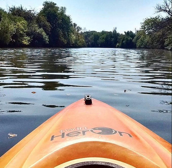 river and trees over the prow of a kayak