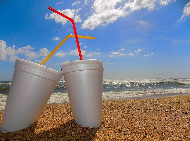 styrofoam cups with straws on beach