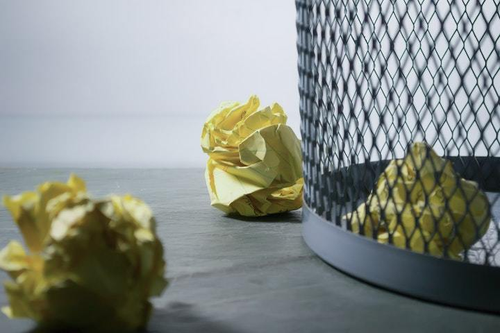 Trash bin containing crumpled yellow paper