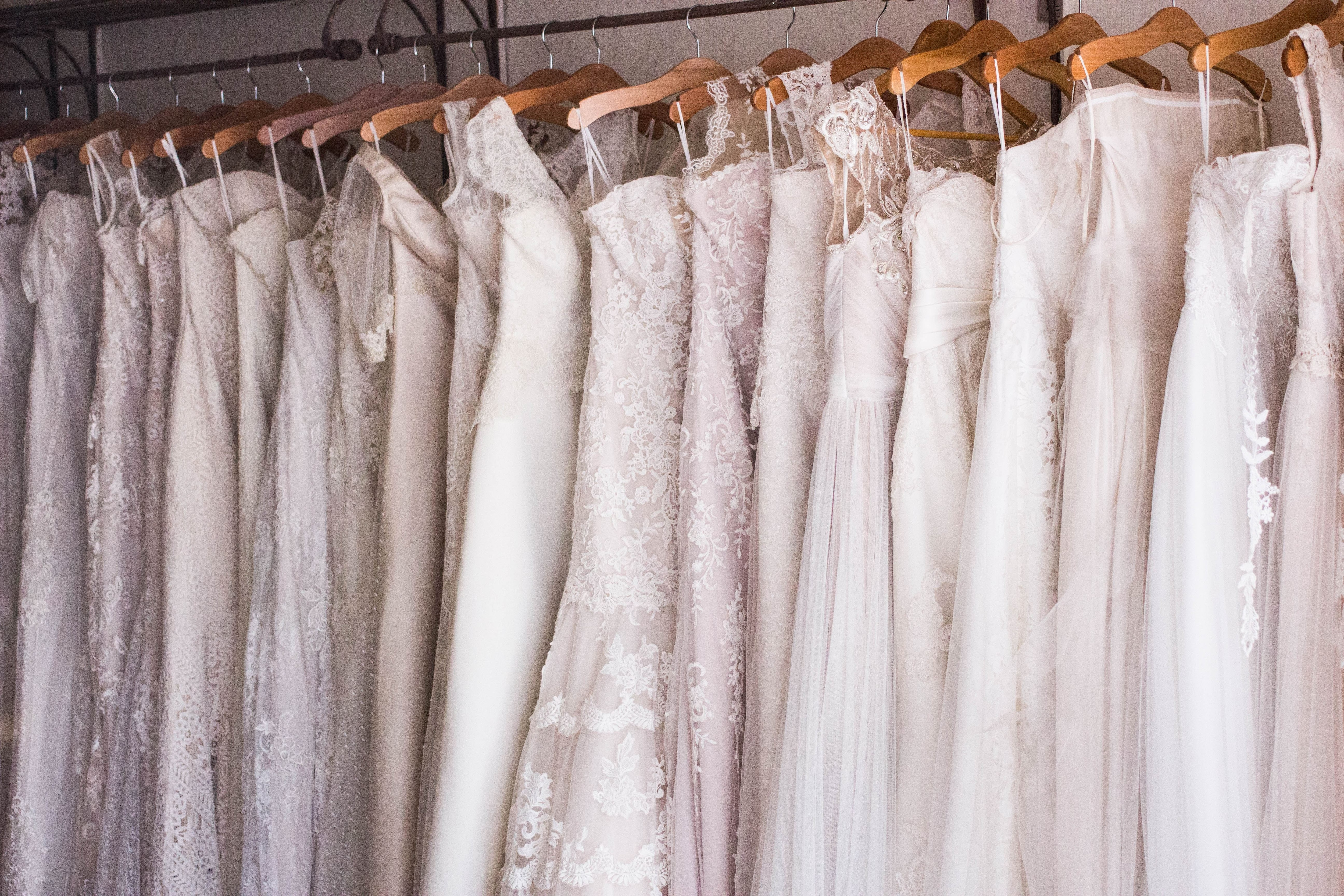 wedding dresses hanging on rack side by side on wooden hangers