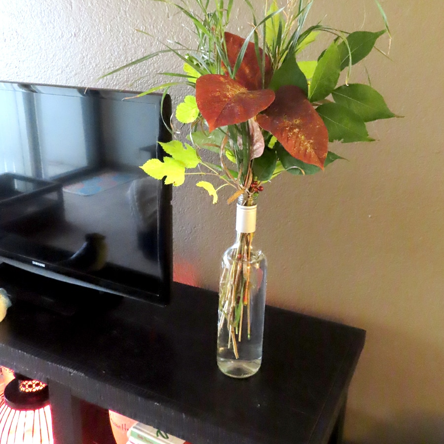 wine bottle as a vase for fall leaves
