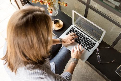 woman using laptop to send email invitation to eco-friendly party at home