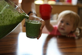 A child reaches for a green smoothie an adult is pouring