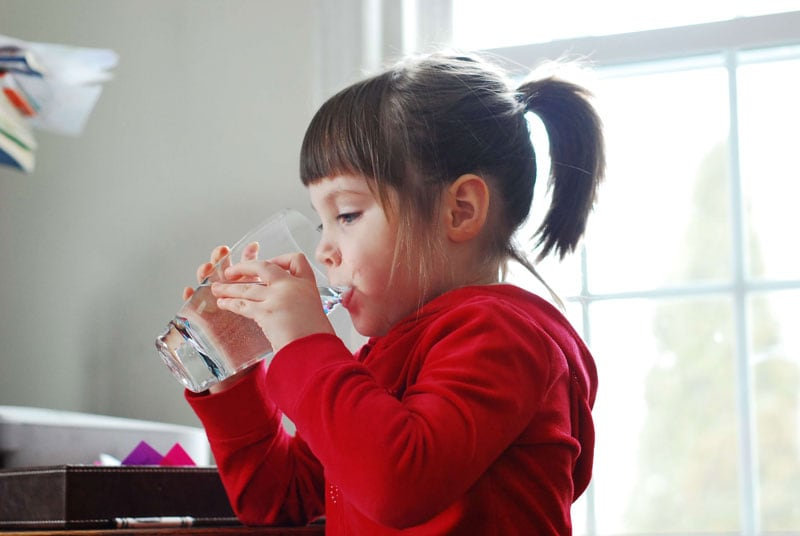 Child drinking water to avoid chapped skin