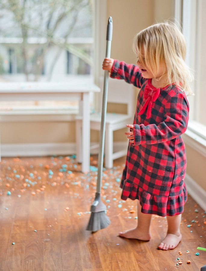 A little girl sweeps the floor