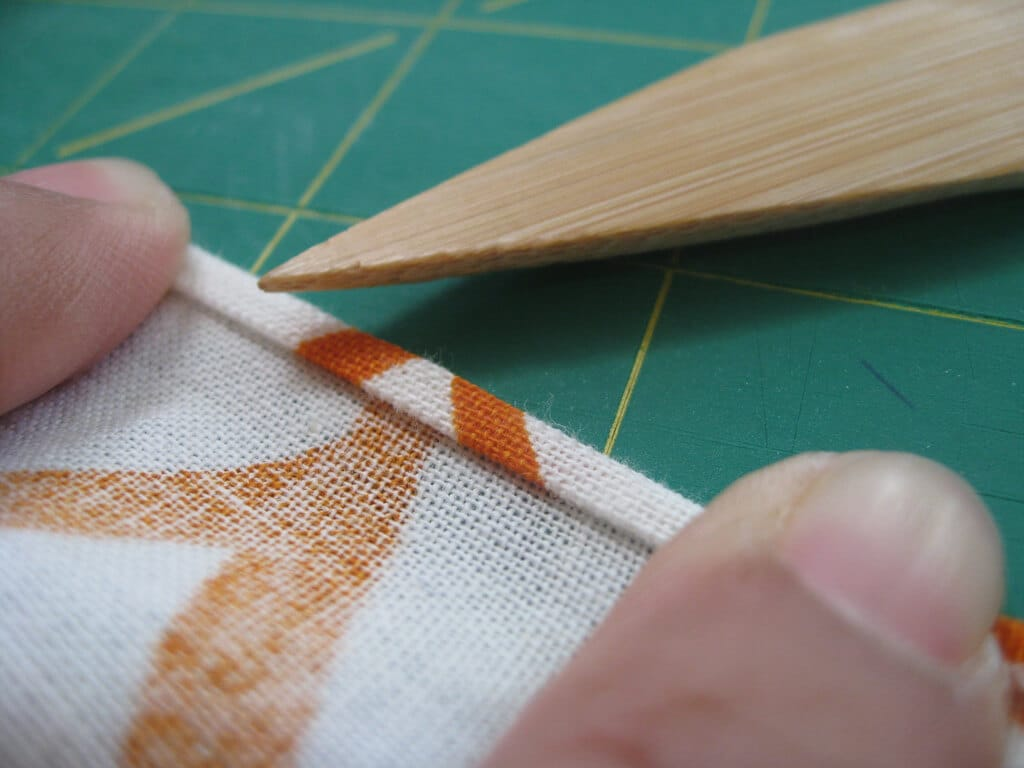 A striped orange and white cloth napkin ready to be sewn on a table