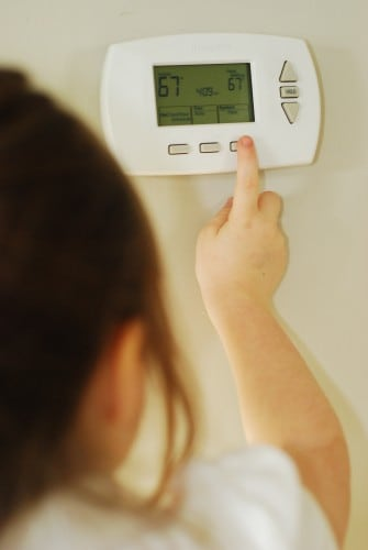 A young girl adjusts the thermostat